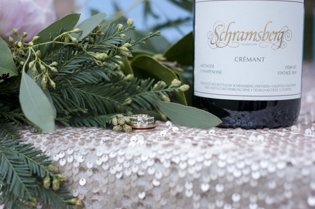 Wedding ring close up with wine and greenery by Jen Vazquez Photography gilroy wedding redwood retreat